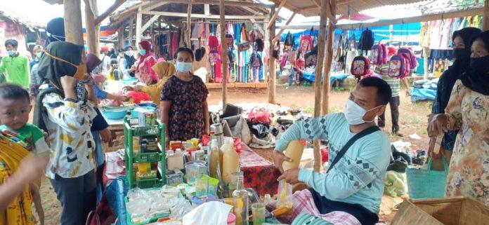 Disaksikan Camat, Aparatur Desa Negri Campang Jaya Bagikan Masker di Pasar